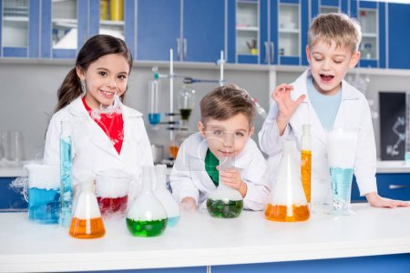 Photo for Three kids in white coats making chemical experiment in laboratory - Royalty Free Image