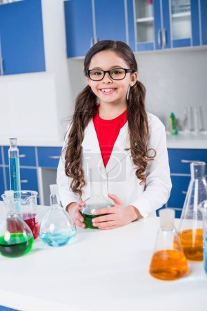 Photo for Little girl in white coat standing at the table with chemical samples in laboratory - Royalty Free Image