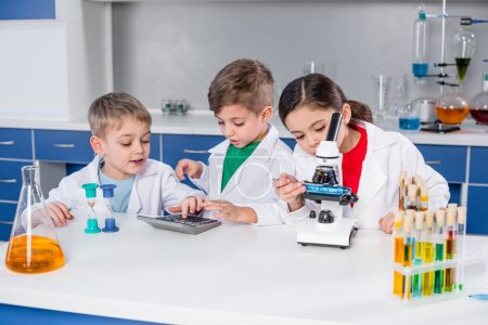 Photo pour Enfants en blouse blanche au microscope et calculatrice en laboratoire chimique - image libre de droit