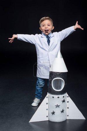 Photo pour Joyeux petit garçon en manteau blanc debout près de la fusée jouet à bras ouverts - image libre de droit