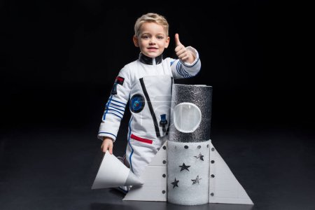 Photo for Smiling little boy astronaut in space suit kneeling near toy spaceship and showing thumb up - Royalty Free Image