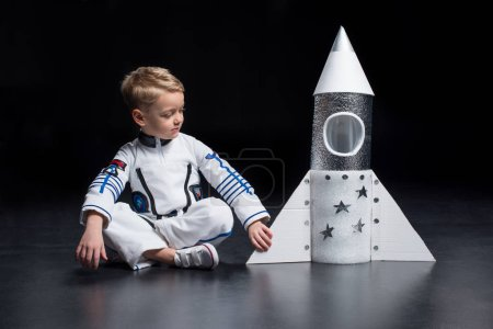 Photo for Little boy astronaut in space suit sitting and looking at toy spaceship - Royalty Free Image