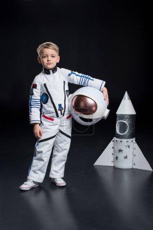 Photo pour Petit garçon astronaute en combinaison spatiale debout près de la fusée et tenant un casque - image libre de droit