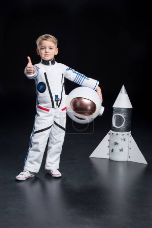 Photo for Little boy astronaut in space suit holding helmet and showing thumb up - Royalty Free Image