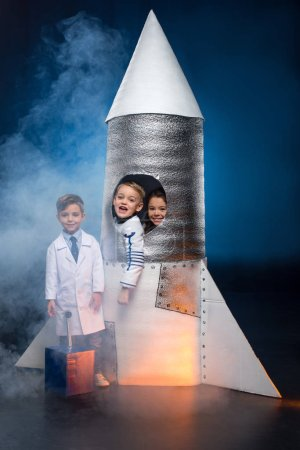 Photo for Three adorable little kids playing astronauts and launching spaceship - Royalty Free Image