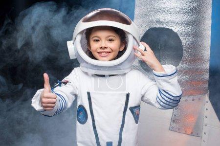 Photo pour Petite fille mignonne en costume d'astronaute montrant pouce levé et souriant à la caméra - image libre de droit