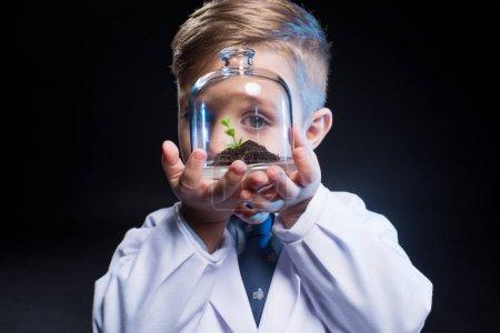 Photo pour Petit garçon en blouse de laboratoire montrant terrarium pot avec la plante fraîche sur fond noir - image libre de droit
