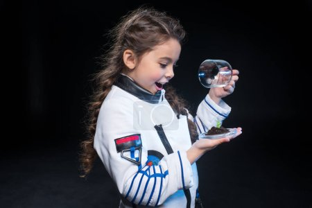 Girl astronaut holding plant