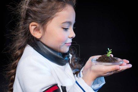 Girl astronaut holding plant