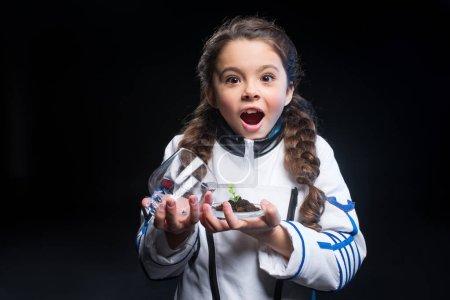 Photo pour Petite fille excitée en costume d'astronaute tenant une plante fraîche dans le sol regardant la caméra - image libre de droit