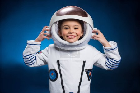 Photo for Little girl in space suit wearing helmet  and smiling at camera - Royalty Free Image