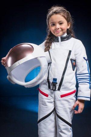 Photo pour Petite fille en combinaison spatiale tenant casque et souriant à la caméra - image libre de droit