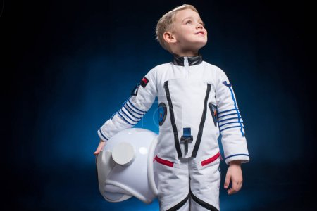 Photo for Cute little boy in space suit holding helmet and looking at distance - Royalty Free Image