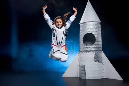 Photo for Happy little girl in astronaut costume jumping near rocket - Royalty Free Image