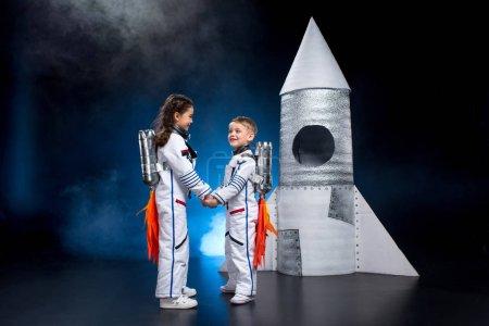 Photo for Little boy and girl in astronaut costumes holding hands and smiling at each other - Royalty Free Image