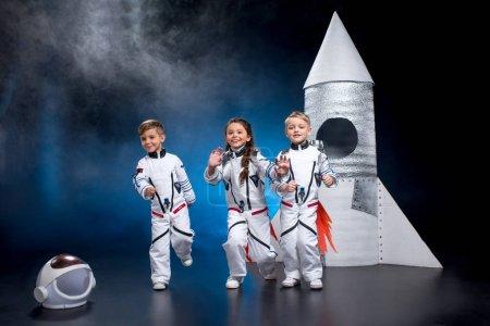 Photo pour Deux petits garçons et une fille dans l'espace costumes courir et sourire à la caméra - image libre de droit