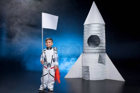 Photo pour Petit garçon astronaute en combinaison spatiale avec drapeau debout près de la fusée - image libre de droit