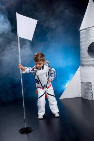 Photo for Little boy astronaut in space suit with flag standing near rocket - Royalty Free Image