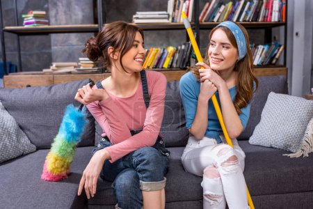 Photo for Smiling young women holding cleaning tools and looking at each other - Royalty Free Image