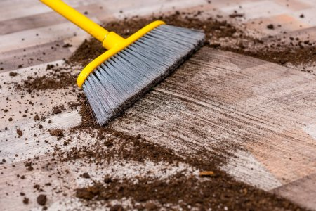 Photo for Close-up view of broom sweeping floor with soil - Royalty Free Image