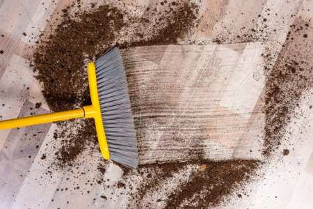 Photo for Close-up top view of broom sweeping floor with soil - Royalty Free Image