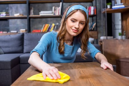 Photo for Young smiling woman wiping table with yellow rag - Royalty Free Image