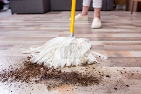 Photo for Close-up view of woman with mop cleaning floor with soil - Royalty Free Image