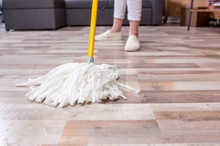 Photo for Close-up partial view of woman cleaning floor with mop - Royalty Free Image