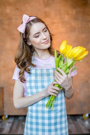 Photo pour Attrayant jeune jardinier femelle tenant des fleurs de tulipes jaunes et souriant - image libre de droit