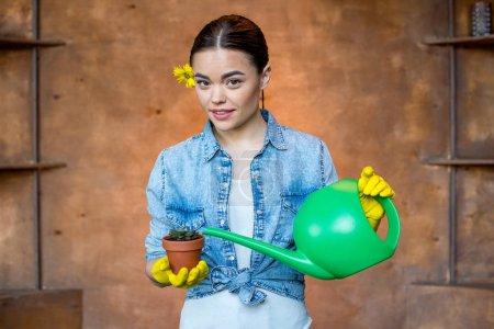 Photo pour Belle jeune femme arrosage plante avec arrosoir - image libre de droit