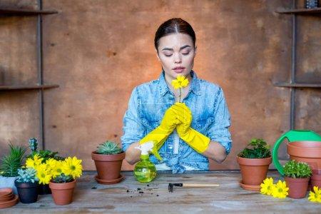 Photo pour Magnifique jeune jardinière en gants de protection tenant fleur jaune - image libre de droit