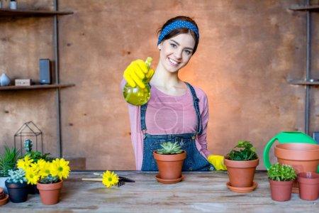 Photo pour Belle jeune jardinière tenant un vaporisateur et souriant à la caméra - image libre de droit