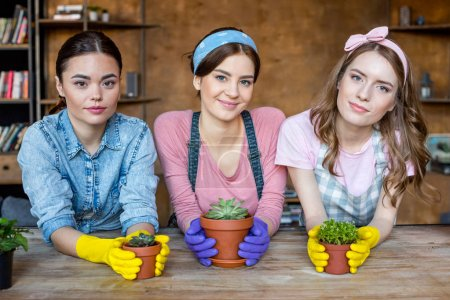 Photo for Beautiful young women in rubber gloves with plants in flowerpots looking to camera - Royalty Free Image