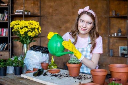 Photo pour Souriant jeune femme en gants de caoutchouc arrosage plante en pot de fleurs et regardant à la caméra - image libre de droit