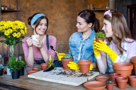 Photo pour Joyeuses jeunes femmes planter des fleurs en pots - image libre de droit