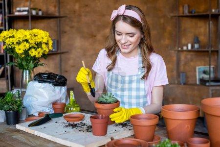 Photo pour Sourire belle jeune femme en gants en caoutchouc avec pelle de jardin et plante en pot de fleurs sur la table - image libre de droit