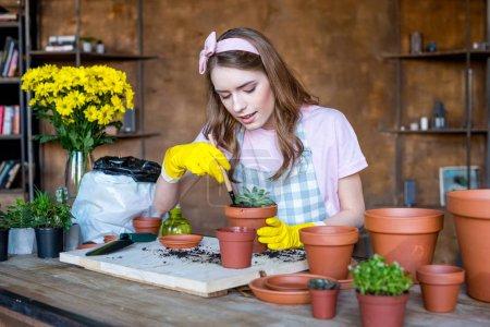 Photo pour Belle jeune femme en gants en caoutchouc avec pelle de jardin et plante en pot de fleurs sur la table - image libre de droit