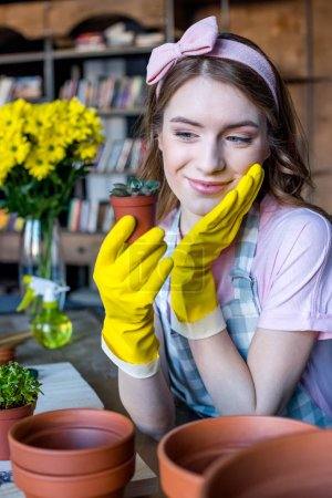 Photo pour Joyeuse belle jeune femme en gants en caoutchouc tenant la plante verte dans le pot de fleurs - image libre de droit
