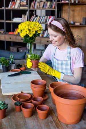 woman holding plant in flowerpot