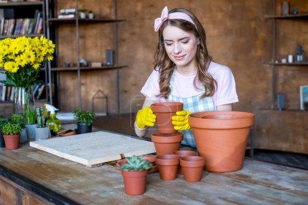 Photo pour Sourire belle jeune femme en gants en caoutchouc tenant pot de fleurs vide - image libre de droit