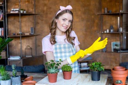 Photo pour Sourire belle jeune femme portant des gants en caoutchouc avec des plantes dans des pots de fleurs sur une table en bois - image libre de droit