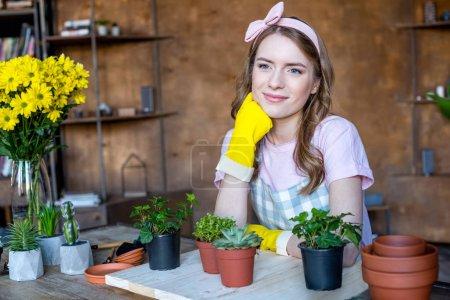 Photo pour Souriant belle jeune femme avec des plantes dans des pots de fleurs sur une table en bois regardant loin - image libre de droit