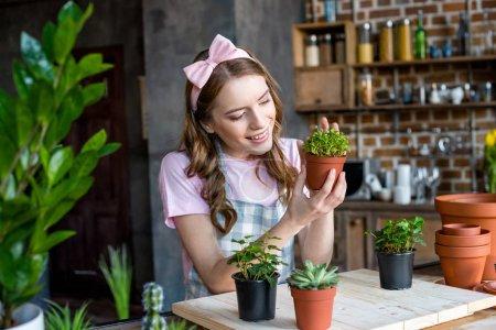 Photo pour Sourire belle jeune femme tenant la plante verte dans le pot de fleurs - image libre de droit