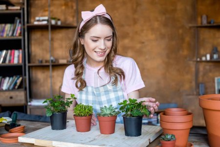 Photo for Cheerful beautiful young woman with plants in flowerpots on wooden table - Royalty Free Image