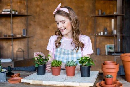 Photo pour Joyeuse belle jeune femme avec des plantes dans des pots de fleurs sur une table en bois - image libre de droit