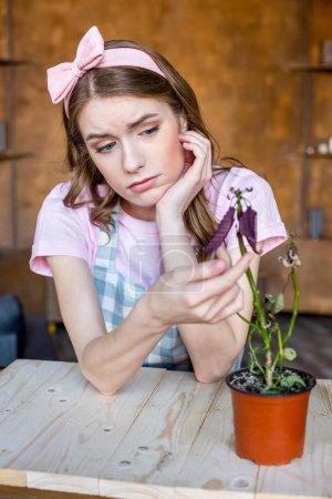 Photo pour Bouleversé jeune femme avec plante en pot de fleurs sur la table - image libre de droit
