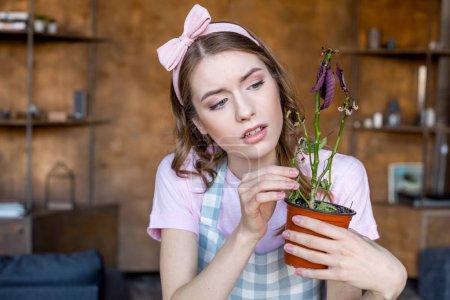 Photo pour Chère jeune femme tenant la plante dans le pot de fleurs dans les mains - image libre de droit