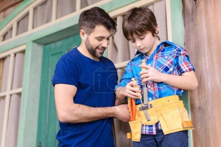 Photo for Smiling father looking at son standing in tool belt and holding tools - Royalty Free Image