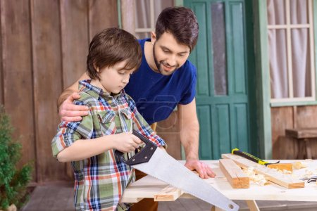 Photo for Smiling father looking at concentrated son sawing wooden plank - Royalty Free Image