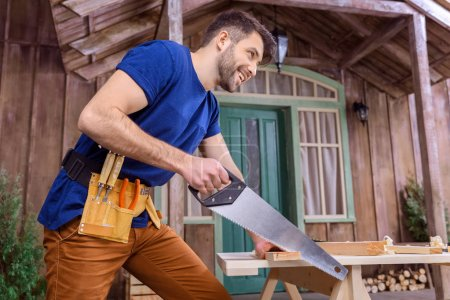 Photo for Low angle view of smiling bearded carpenter in tool belt sawing wooden plank on porch - Royalty Free Image
